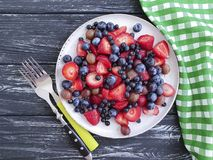 Il piatto delle fragole, mirtilli, vitamina ha ordinato l'estate antiossidante organica del prodotto delle uva spina su un fondo  fotografie stock libere da diritti