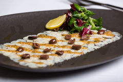 Il piatto di pesce è servito con i dadi, la rucola ed il limone Immagini Stock