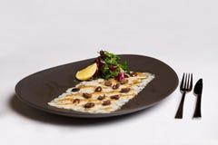 Il piatto di pesce è servito con i dadi, la rucola ed il limone Fotografia Stock Libera da Diritti