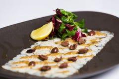 Il piatto di pesce è servito con i dadi, la rucola ed il limone Immagini Stock Libere da Diritti