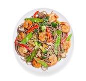 Il piatto di scalpore ha fritto le tagliatelle con i gamberetti e le verdure isolati su fondo bianco immagini stock
