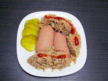 Il piatto finito che consiste del porridge, delle salsiccie, dei sottaceti e del ketchup del grano saraceno immagine stock libera da diritti