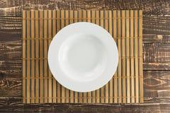Il piatto vuoto bianco su tessuto di bambù ed il legno presentano il fondo dentro Fotografia Stock