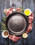 Il piatto vuoto con il lombo crudo dell'agnello taglia la carne, il petrolio, l'erba e le spezie a pezzi su fondo di legno blu immagine stock libera da diritti