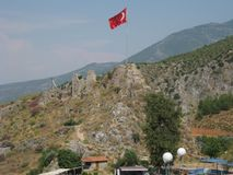 Il picco di montagna con le rovine di vecchie casa e bandiera del turco fotografie stock libere da diritti