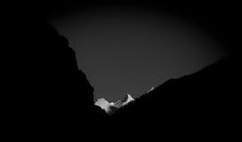 Il picco di montagna di Snowy si è acceso dalla priorità alta della siluetta e del sole Immagine Stock
