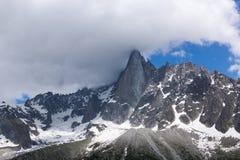 Il picco sulla montagna in alpi francesi è coperto di nuvole piovose Immagine Stock