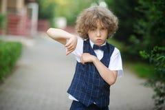 Il piccolo allievo è nel cortile della scuola con un'espressione arrabbiata sul suo fronte Immagini Stock Libere da Diritti