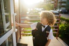 Il piccolo allievo in uniforme scolastico apre la porta Fotografie Stock Libere da Diritti