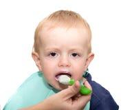 Il piccolo bambino è alimentato con il cottage, ma non vuole mangiare Fotografia Stock Libera da Diritti