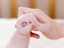 Il piccolo bambino è tenuto dalla mano immagini stock