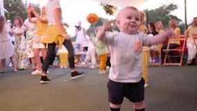Il piccolo bambino allegro salta ed ondeggiando le sue mani su fondo unfocused del primo piano della gente video d archivio