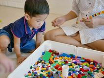 Il piccolo bambino asiatico che è mattoni di plastica di collegamento variopinti di sguardo interessati gioca fotografia stock libera da diritti