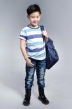 Il piccolo bambino asiatico che sta con una borsa di corredo lanciata sopra la sua dovrebbe Immagini Stock