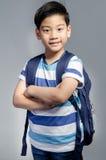 Il piccolo bambino asiatico che sta con una borsa di corredo lanciata sopra la sua dovrebbe Fotografia Stock Libera da Diritti