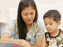 Il piccolo bambino asiatico gode di di ascoltare sua madre che legge ad alta voce un libro a lei fotografie stock