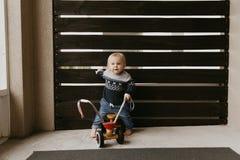 Il piccolo bambino biondo sveglio adorabile prezioso del ragazzo del bambino del bambino che gioca fuori su Toy Bicycle Scooter M fotografie stock libere da diritti