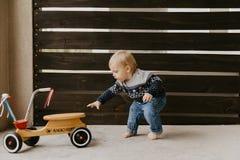 Il piccolo bambino biondo sveglio adorabile prezioso del ragazzo del bambino del bambino che gioca fuori su Toy Bicycle Scooter M fotografia stock libera da diritti