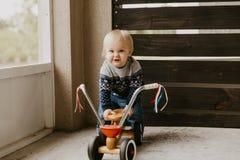 Il piccolo bambino biondo sveglio adorabile prezioso del ragazzo del bambino del bambino che gioca fuori su Toy Bicycle Scooter M immagini stock