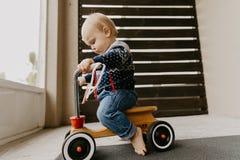 Il piccolo bambino biondo sveglio adorabile prezioso del ragazzo del bambino del bambino che gioca fuori su Toy Bicycle Scooter M fotografie stock