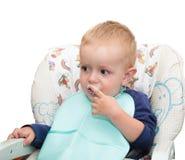 Il piccolo bambino biondo in una sedia dei bambini ed in un suolo della busbana francese Fotografie Stock