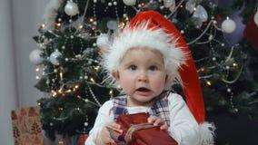 Il piccolo bambino in cappello di Santa gioca con un regalo archivi video