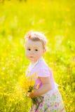 Il piccolo bambino che gioca con il campo fiorisce il giorno dell'estate o della primavera Immagini Stock