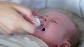Il piccolo bambino che si trova in greppia, la ragazza che grida, madre dà al bambino una tettarella stock footage
