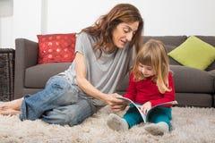 Il piccolo bambino e la madre che leggono un racconto prenotano a casa fotografia stock libera da diritti