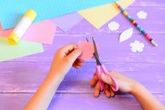 Il piccolo bambino fa una cartolina d'auguri per la mamma Scherzi giudica le forbici disponibile e taglia un fiore da carta punto Immagine Stock