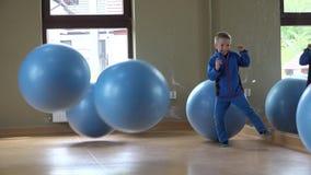 Il piccolo bambino felice al gioco della palestra con le grandi palle, molte palla non colpisce il ragazzo agile archivi video