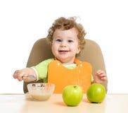 Il piccolo bambino mangia con il cucchiaio che si siede alla tavola con Fotografie Stock