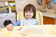 Il piccolo bambino mangia il porridge del grano Fotografie Stock