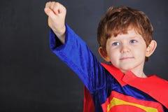 Il piccolo bambino in mantello rosso, sta la lavagna vicina Fotografia Stock