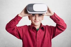 Il piccolo bambino maschio bello indossa i vetri di VR, si diverte e si intrattiene, gioca i video giochi, isolati sopra fondo bi Fotografia Stock