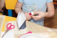 Il piccolo bambino passa a colla i mestieri di carta allo scrittorio della scuola Fotografia Stock