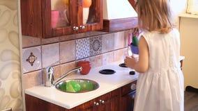 Il piccolo bambino prescolare attivo dell'età, ragazza sveglia del bambino con capelli ricci biondi, mostra il gioco della cucina stock footage