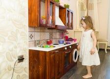 Il piccolo bambino prescolare attivo dell'età, ragazza sveglia del bambino con capelli ricci biondi, mostra il gioco della cucina Immagine Stock