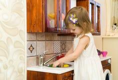 Il piccolo bambino prescolare attivo dell'età, ragazza sveglia del bambino con capelli ricci biondi, mostra il gioco della cucina Immagine Stock Libera da Diritti