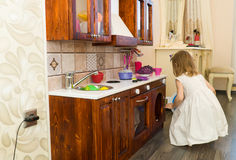 Il piccolo bambino prescolare attivo dell'età, ragazza sveglia del bambino con capelli ricci biondi, mostra il gioco della cucina Immagini Stock
