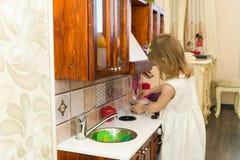 Il piccolo bambino prescolare attivo dell'età, ragazza sveglia del bambino con capelli ricci biondi, mostra il gioco della cucina Fotografia Stock Libera da Diritti