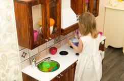 Il piccolo bambino prescolare attivo dell'età, ragazza sveglia del bambino con capelli ricci biondi, mostra il gioco della cucina Immagini Stock Libere da Diritti