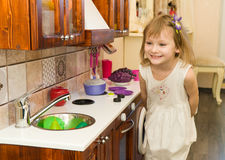 Il piccolo bambino prescolare attivo dell'età, ragazza sveglia del bambino con capelli ricci biondi, mostra il gioco della cucina Fotografia Stock