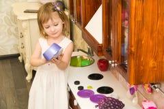 Il piccolo bambino prescolare attivo dell'età, ragazza sveglia del bambino con capelli ricci biondi, mostra il gioco della cucina Fotografie Stock