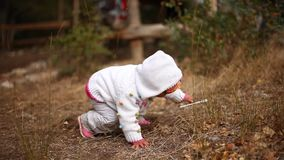 Il piccolo bambino prova a stare su dalla terra ed a prendere un bastone di plastica video d archivio