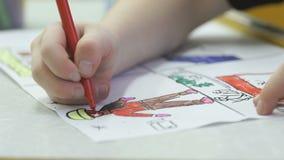 Il piccolo bambino sconosciuto dipinge le immagini con la penna a feltro stock footage