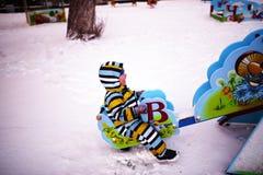 Il piccolo bambino scuote su oscillazione al campo da giuoco nell'inverno Immagini Stock Libere da Diritti