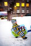 Il piccolo bambino scuote su oscillazione al campo da giuoco nell'inverno Fotografia Stock