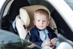 Il piccolo bambino si siede in automobile e nel sorriso alla macchina fotografica Fotografia Stock