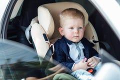 Il piccolo bambino si siede in automobile e nel sorriso alla macchina fotografica Immagini Stock Libere da Diritti